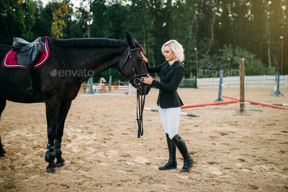 Young woman in jockey uniform stroking a horse - Stock Photo - Images