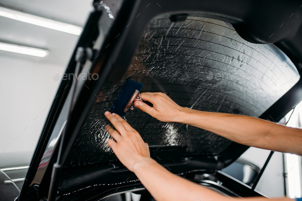 Specialist with drier, tinting film installation - Stock Photo - Images