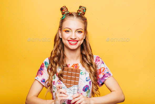 Young smiling lady holds chocolate bar - Stock Photo - Images