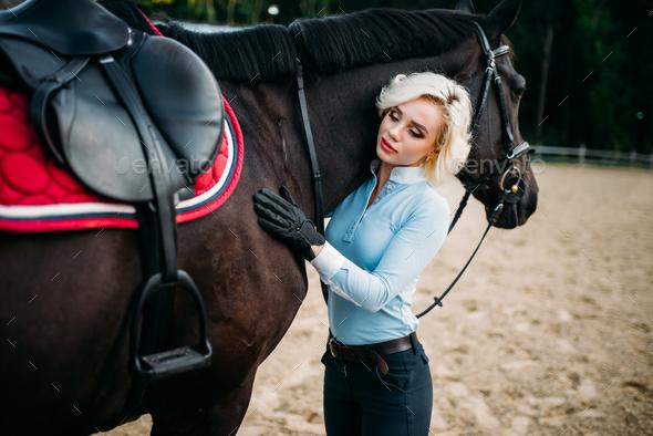 Female rider hugs her horse, horseback riding - Stock Photo - Images