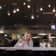Woman Posing at Counter in Bar and Talking Phone Drinking Coffee