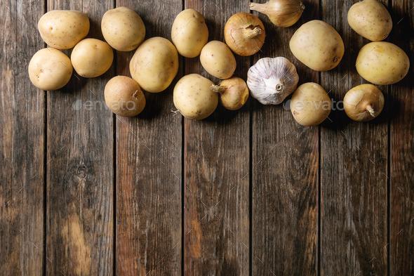 Raw organic potatoes and onion - Stock Photo - Images