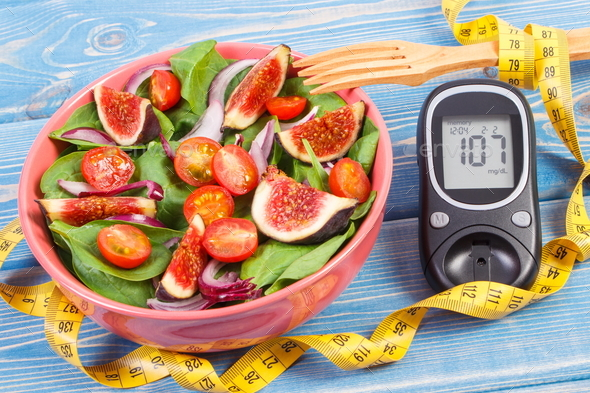 Fruit and vegetable salad and glucometer with tape measure - Stock Photo - Images