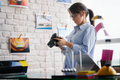 Photographer Working And Checking Digital Camera Settings In Office - PhotoDune Item for Sale