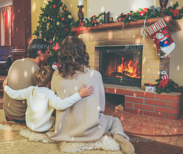 Family near fireplace in decorated house interior - Stock Photo - Images