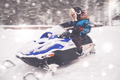Boy driving snowmobile in a winter landscape - PhotoDune Item for Sale