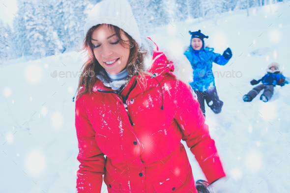 Happy mother with her children playing in a snow - Stock Photo - Images
