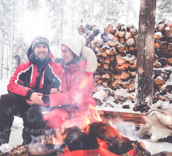 Couple near bonfire in winter landscape - Stock Photo - Images