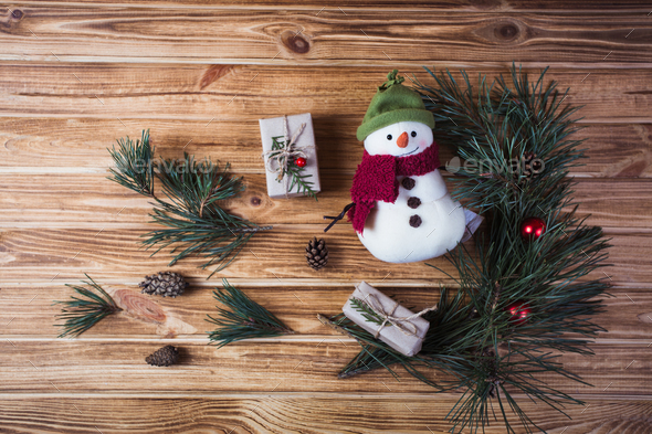 Christmas decorations on fir tree branches with gift boxes and snowman cookie on wooden table - Stock Photo - Images