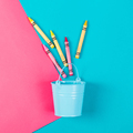 Blue bucket with color pencils on a blue pink background.