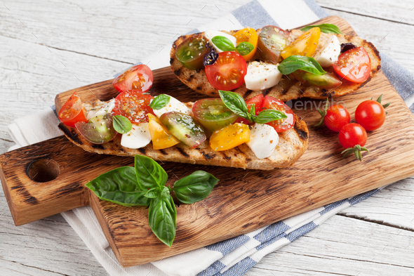 Bruschetta with tomatoes, mozzarella and basil - Stock Photo - Images