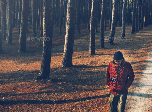 Man walking alone through the forest - Stock Photo - Images