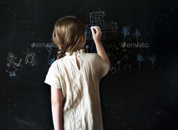 Little girl drawing on a blackboard - Stock Photo - Images