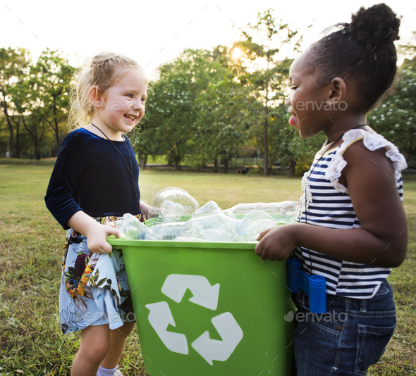 Responsible little girls cleaning at the park - Stock Photo - Images