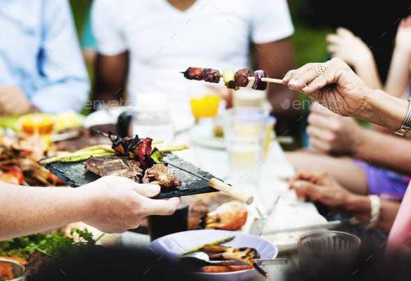 Group of people having BBQ party outdoors - Stock Photo - Images