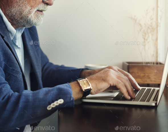 Elderly man is using computer laptop - Stock Photo - Images
