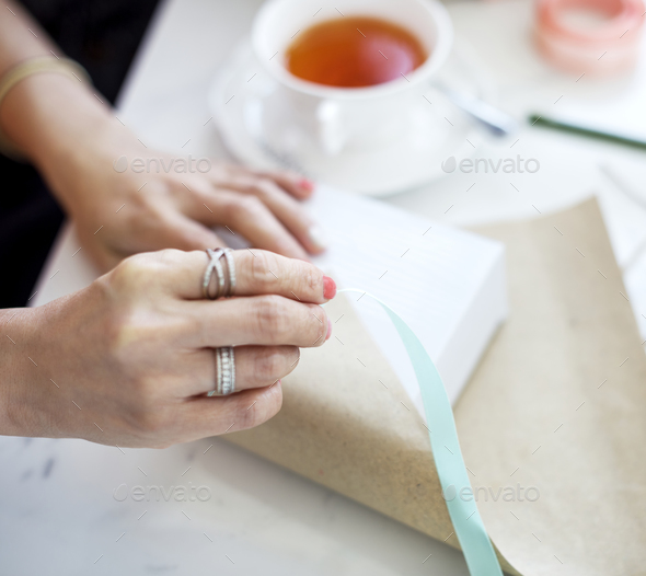 Hands are wrapping gift box - Stock Photo - Images
