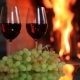Two Glasses of Red Wine with Grapes Near the Fireplace in the Evening - VideoHive Item for Sale