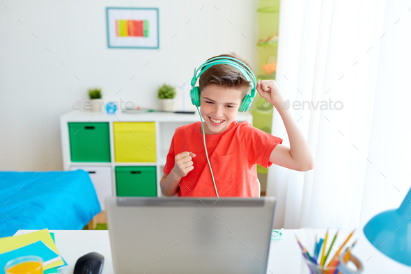 boy in headphones playing video game on laptop - Stock Photo - Images