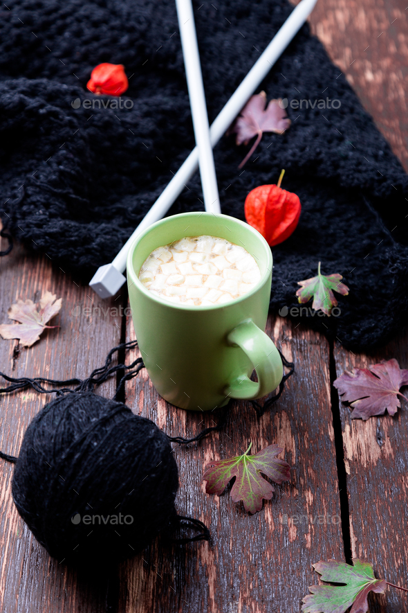 Cup of coffee or hot chocolate with marshmallow near knitted blanket and knitting needles. - Stock Photo - Images