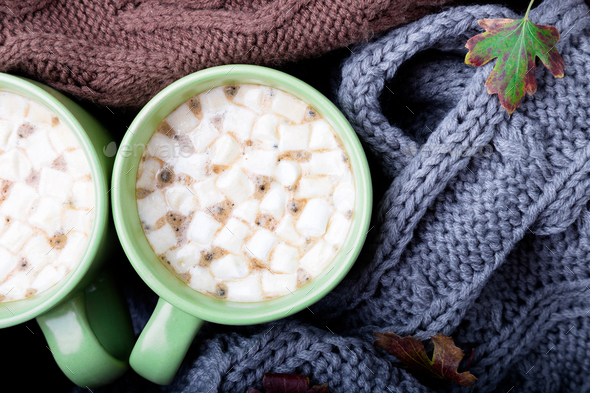 Two cup of coffee or hot chocolate with marshmallow near three knitted weater or  knitted blanket.  - Stock Photo - Images