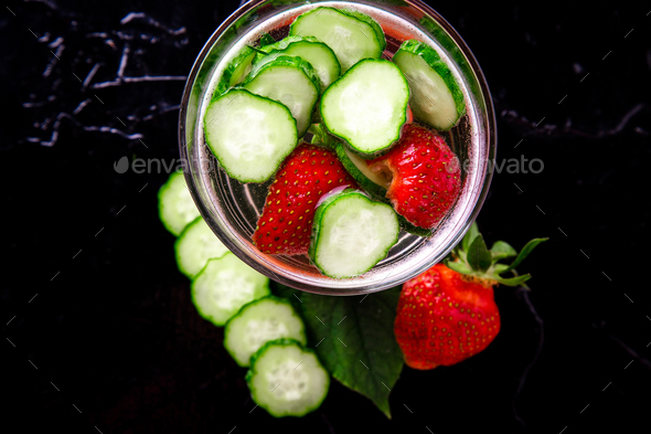 Cucumber and strawberry detox water in glass on black background. Diet. Top view. - Stock Photo - Images