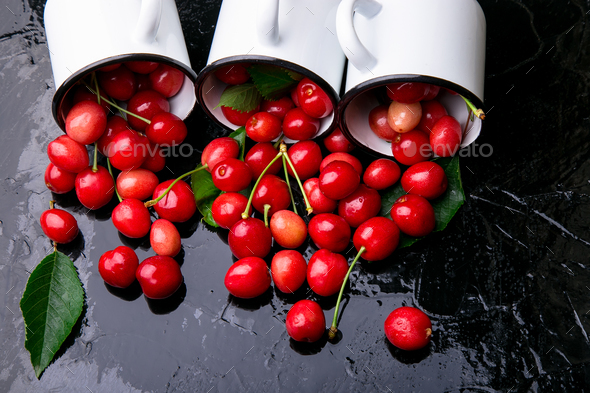 Scattered cherry from enamel cups. - Stock Photo - Images
