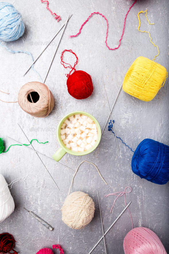 Multicolor knitting ball and needles around green cup of coffee - Stock Photo - Images