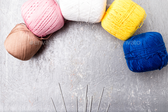 Multicolor knitting ball and needles on grey background. Top view. Copy space. Knitting yarn. - Stock Photo - Images