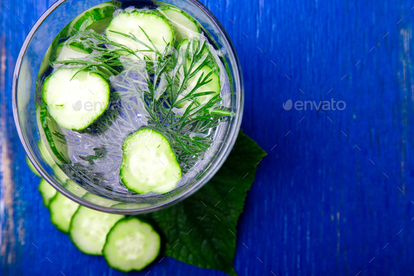 Cucumber water   in glass with dill on blue wooden background. Detox, diet. Top view. Copy space - Stock Photo - Images