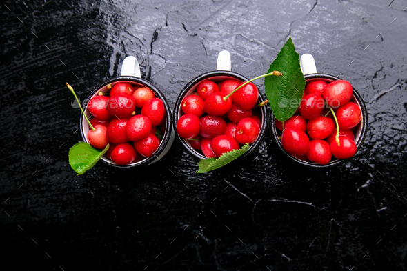 Cherry in enamel cup on black background. Healthy, summer fruit. Cherries. Top view. - Stock Photo - Images