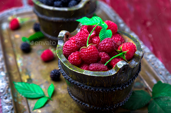 Red raspberry with leaf in a basket on vintage metal tray. Close up. - Stock Photo - Images