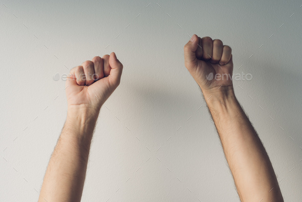 Clenched fists and arms raised in victorious manner - Stock Photo - Images