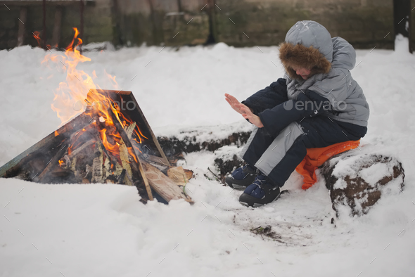 boy sitting by fire in the street - Stock Photo - Images