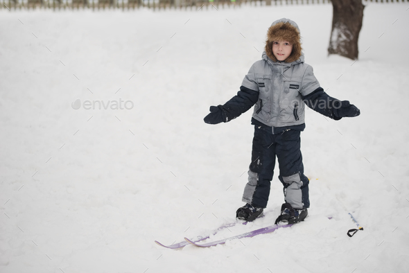 boy riding ski in winter yard - Stock Photo - Images