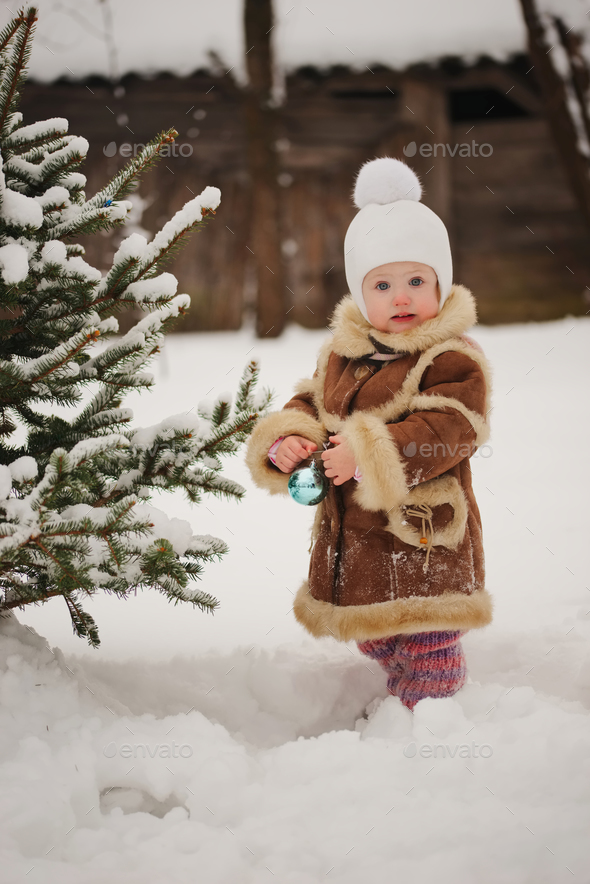 girl decorating christmas tree n the yard - Stock Photo - Images