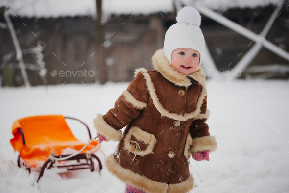 cute girl with sled in snow - Stock Photo - Images