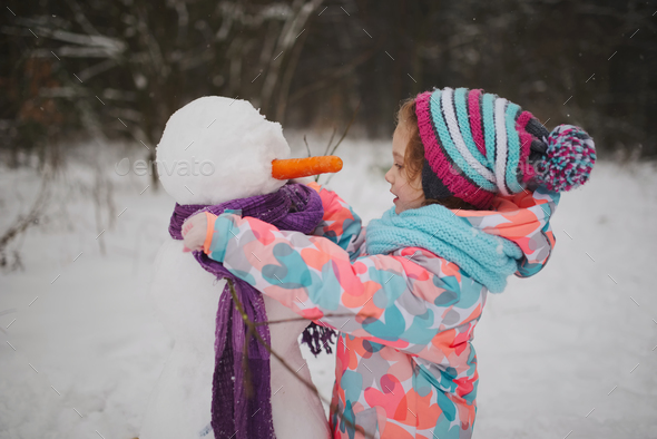 girl makes snowman in winter park - Stock Photo - Images