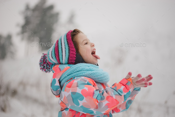 little girl catching snowflakes in winter park - Stock Photo - Images