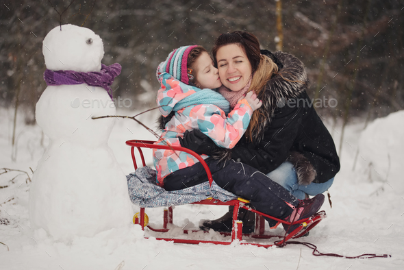 beautiful mother with daughter in winter park - Stock Photo - Images