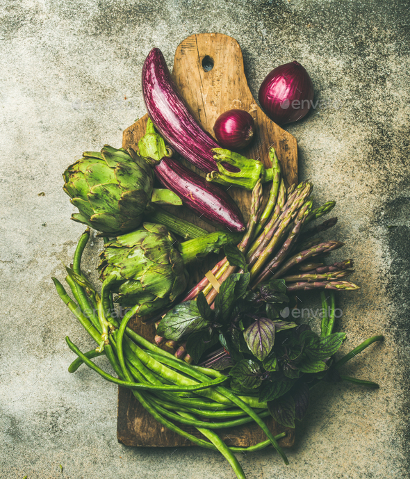 Flat-lay of green and purple vegetables on board, grey background - Stock Photo - Images