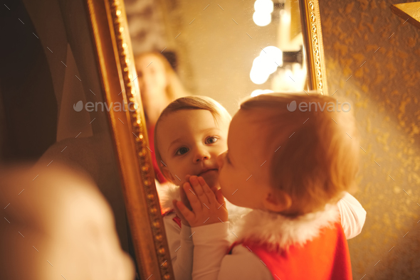 little girl kisses herself in the mirror - Stock Photo - Images