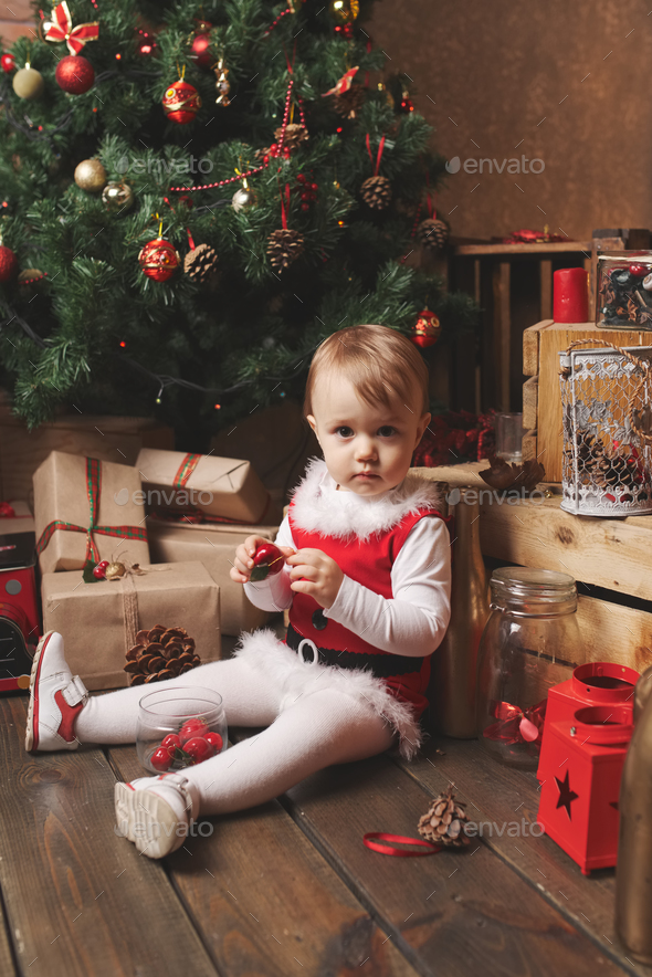 funny girl plays with christmas gifts - Stock Photo - Images