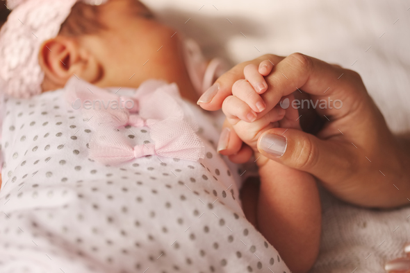 mother holds little hand of newborn baby - Stock Photo - Images