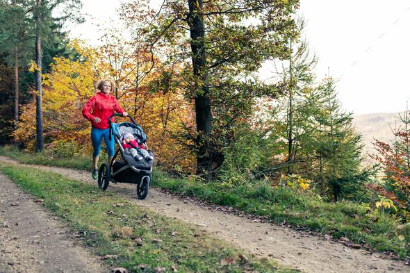 Running mother with stroller enjoying motherhood at autumn sunse - Stock Photo - Images
