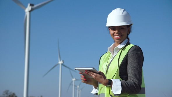 woman with hard hat against wind turbine by framestock videohive