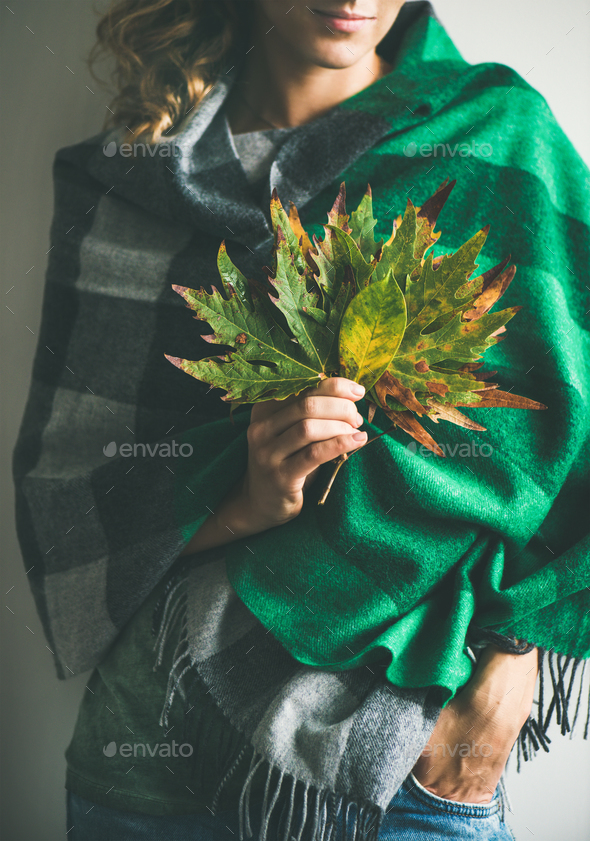 Woman in scarf or blanket and jeans with Autumn leaves - Stock Photo - Images