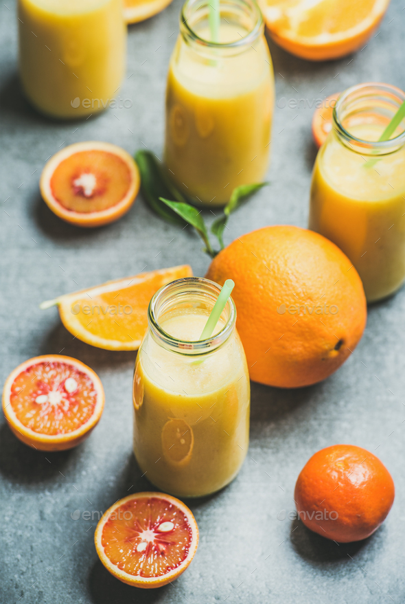 Healthy yellow smoothie in bottle over concrete background - Stock Photo - Images