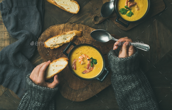 Woman in sweater eating corn soup with prawns, top view - Stock Photo - Images