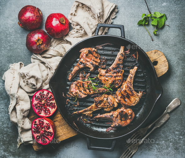 Grilled lamb meat chops served with fresh pomegranates, grey background - Stock Photo - Images